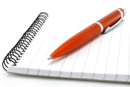 Notepad with orange ball pen on a white background photo