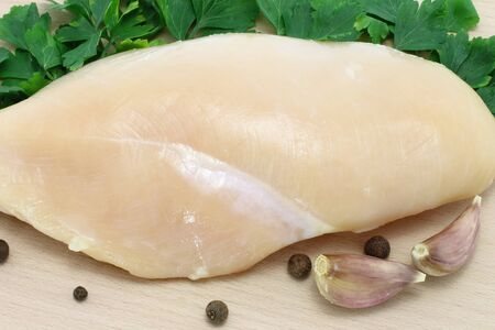 raw chicken on wooden board close-up photo