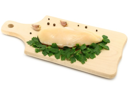 Raw chicken on wooden board on a white background  photo