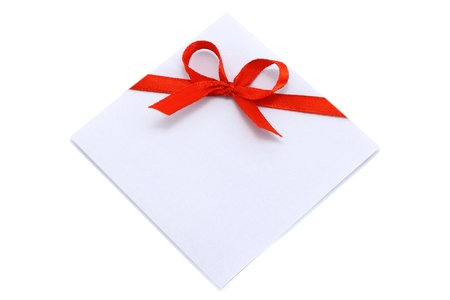 Piece of paper with red bow on a white background photo