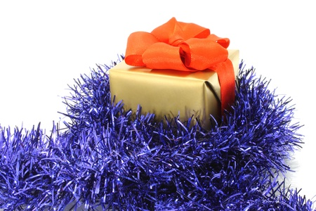 Gold gift box with blue tinsel on white background  photo