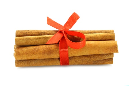 Bunch of cinnamon sticks with red bow on white background  photo