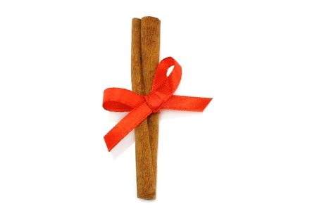 Cinnamon stick with red bow on white background  photo