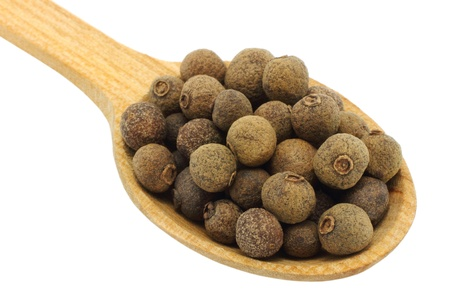 Seeds of allspice in wooden spoon on white background  photo