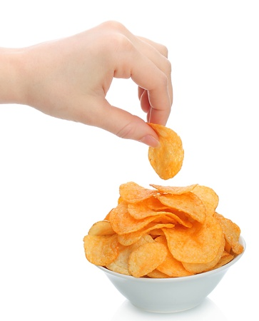 unhealthy snack: Hand holds a potato chip with the bowl of potato chips