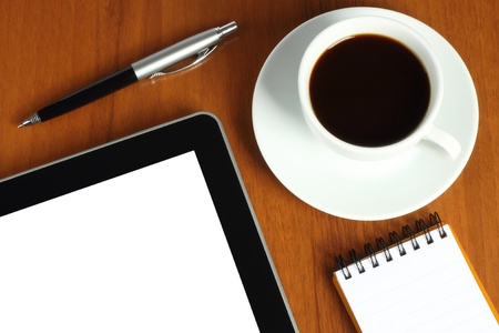 Touch screen device, notepad, pen and cup of coffee on wooden background  photo