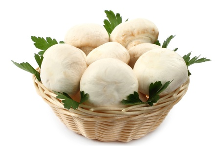 Champignons in wicker plate with parsley on white background Stock Photo - 12918978