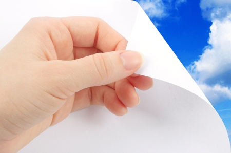 turn over: Blank sheet of paper with hand on sky background Stock Photo
