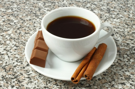 Cup of coffee with chocolate and cinnamon sticks on table top photo