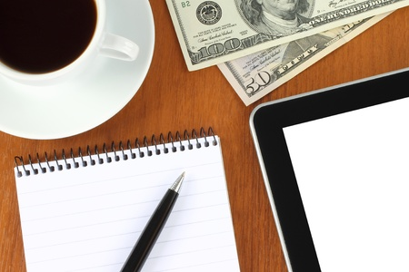 Touch screen device, notepad, pen, money and cup of coffee on wooden background