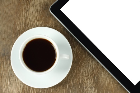 Touch screen device and cup of coffee on old wooden background photo