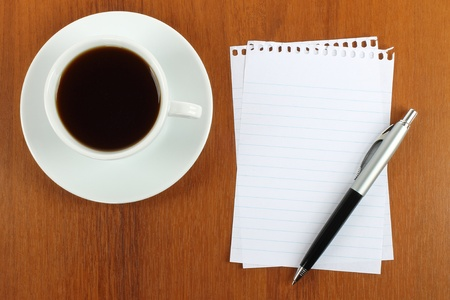 Cup of coffee, paper and pen on wooden background photo