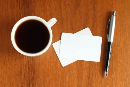 Cup of coffee with business cards and pen Stock Photo