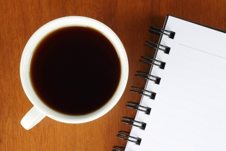 Cup of coffee with notepad on wooden background photo