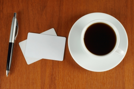 Cup of coffee with business cards and pen photo