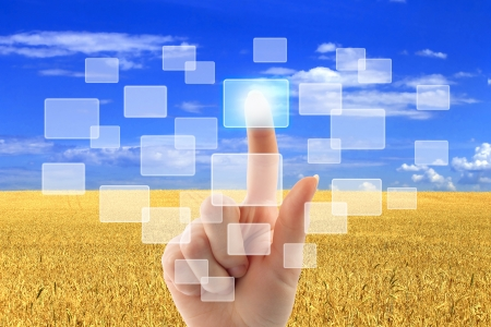 Woman hand pushing virtual icons on interface over wheat field and blue sky landscape photo