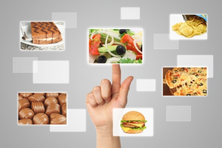 Woman hand uses touch screen interface with food on grey backround photo