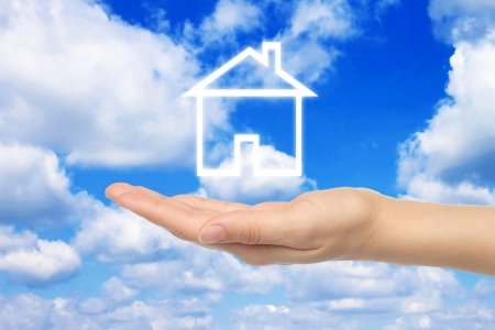 Virtual house with woman hand on sky background  photo
