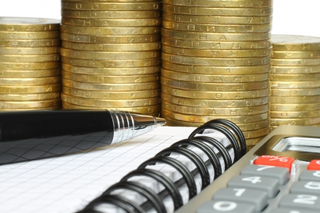 Stationery with stack of coins on white background