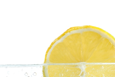 Slice of lemon in water on white background