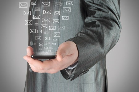 send sms: Businessman uses smart phone with virtual envelopes on grey background