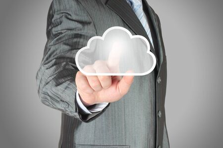 Businessman pushes virtual cloud button  Cloud computing concept photo