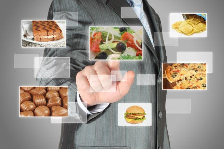 Businessman pushes touch screen button with salad on virtual interface with food  Diet concept photo