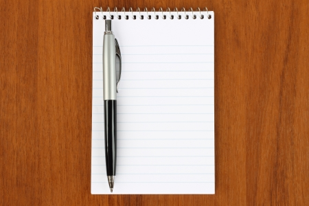 Notepad and pen on wooden background  photo