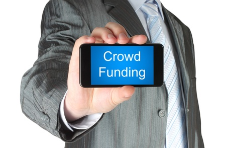 crowd sourcing: Businessman holds smart phone with crowd funding words on its screen isolated on white background