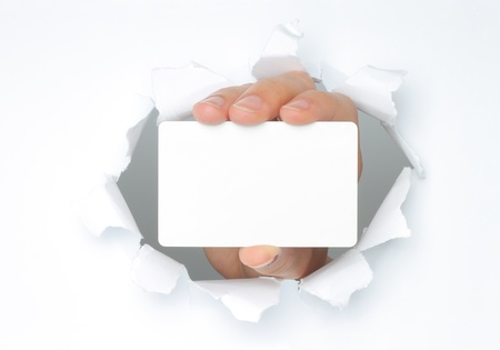 business card in hand: Hand holds white card through white torn paper