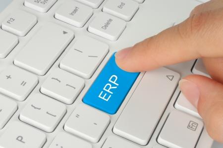 Hand pushing blue ERP  enterprise resource planning  button on white keyboard background