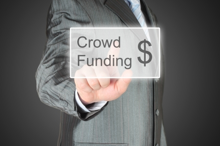 crowd sourcing: Businessman pushes virtual crowd funding button on dark background