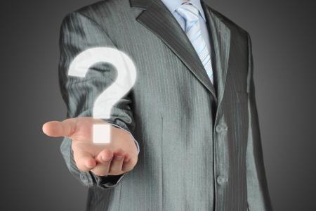 Businessman with question mark on dark background