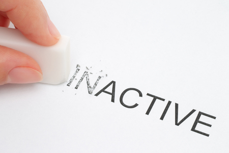 inactive: Hand erasing part of the inactive word close-up  Stock Photo