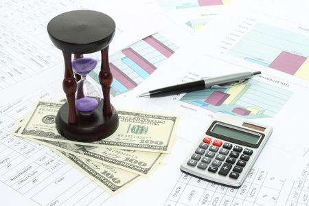 Business composition of graphs, tables, money, sand watch and pen close-up