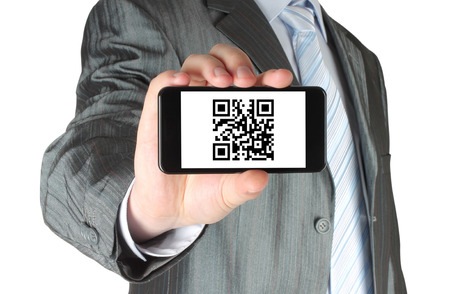 qr code: Businessman holds smart phone with QR code on white background