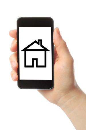 Hand with smart phone and house on white background photo