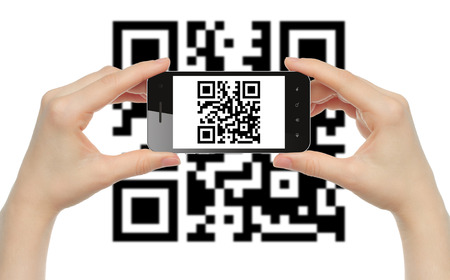 Hands hold smart phone with QR code on white background   photo