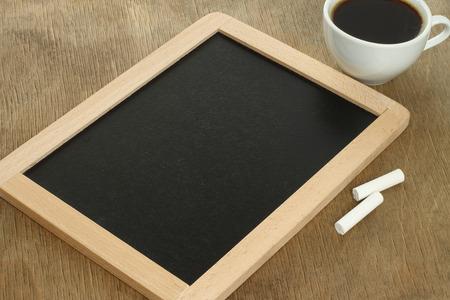 white chalks: Pizarra en blanco con tizas de color blanco y caf� en el fondo de madera Foto de archivo