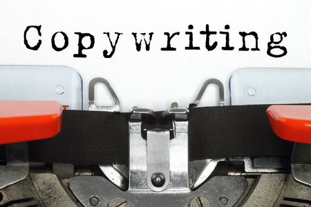 content writing: Part of typing machine with typed copywriting word on white paper