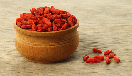 goji berry: Bowl with goji berries on a wooden background close-up  Stock Photo
