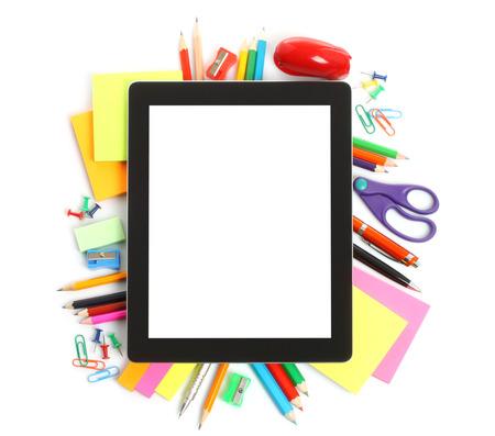 articulos oficina: Tablet PC con suministros de oficina de la escuela en el fondo blanco