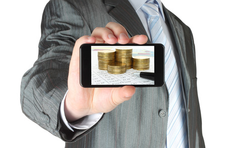 Man holds smart phone with business composition of graphs and money on white background  photo