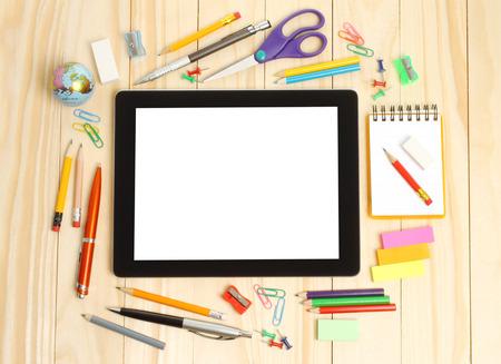 articulos oficina: Tablet PC con suministros de oficina de la escuela sobre fondo de madera Foto de archivo