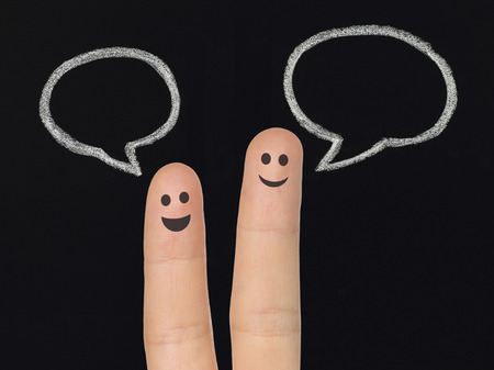 Happy fingers with chalk speech bubbles on blackboard, social media concept   photo