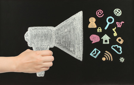 Hand holds chalk megaphone with flying icons drawn on blackboard photo