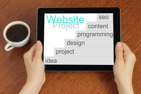 website button: Hand hold tablet pc with website project Stock Photo
