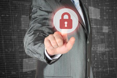 se�ales de seguridad: Hombre de negocios empujando el bot�n de seguridad virtual sobre fondo digital Foto de archivo