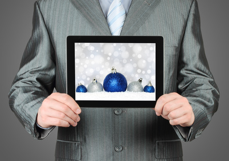 Man holds tablet PC with Christmas composition on dark background photo