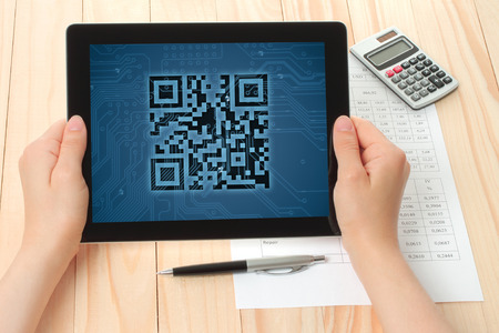 qr code: Hands hold tablet PC with QR code on wooden background